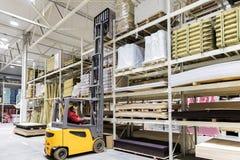 Matériaux de construction de chargement de travailleur d'entrepôt avec le chariot élévateur photos stock