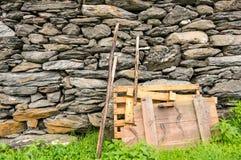 Matériaux en bois se penchant sur un mur en pierre Photo stock