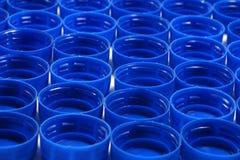 Matériaux recyclables Les chapeaux bleus des bouteilles faites de polyéthylène haute densité de HDPE ont isolé selon des couleurs photo libre de droits