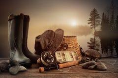 Matériel de pêche de mouche sur le paquet avec le lac brumeux Photo libre de droits