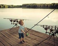 Matériel de pêche Pêcheur de garçon avec les cannes à pêche sur le pilier en bois Photographie stock