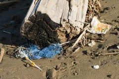Matériel de plastique et d'ordures sur la plage de sable photographie stock libre de droits