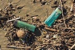 Matériel de plastique et d'ordures sur la plage de sable photos stock