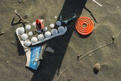 Matériel de plastique et d'ordures sur la plage de sable photo stock