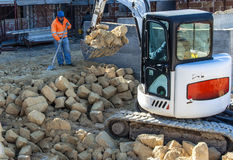 Matériel inerte compact d'excavatrice avec l'assistance d'un travailleur Photo libre de droits