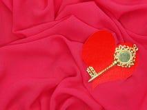 Matériel rouge de satin avec la clé au concept d'amour de forme de coeur Images libres de droits