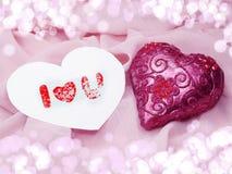 Matériel rouge de satin avec le concept d'amour de forme de coeur Photos stock