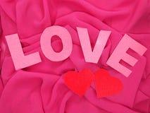 Matériel rouge de satin avec le concept d'amour de forme de coeur Photographie stock