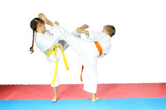 On the mat, a boy and a girl in karategi are doing blows kicks Royalty Free Stock Images