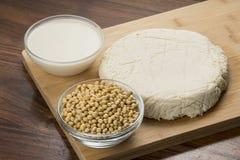 Mat: Bunkar av sojabönor mjölkar, sojabönor och tofuen som isoleras på träbakgrund arkivbild