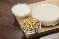 Mat: Bunkar av sojabönor mjölkar, sojabönor och tofuen som isoleras på träbakgrund arkivfoto
