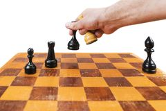 Mat on a chessboard. Male hand rearranges chess pieces on an old chessboard, isolated on a white background, a first person view Stock Photography