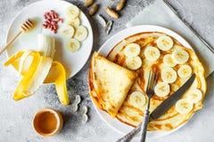 Mat efterrätt, bakelser, pannkaka, paj Smakliga härliga pannkakor med bananen och honung arkivfoto