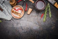 Mat eller matlagningbakgrund med örter, kryddor, köttgaffel och kniv och exponeringsglas av rött vin på mörk lantlig metallbakgru Royaltyfria Bilder