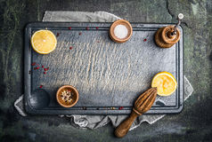 Mat eller matlagningbakgrund med salt, peppar och citronen på gutting bräde för grå tappning Royaltyfri Fotografi