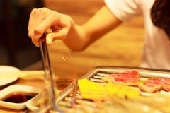 Mat för hållande rostfritt stål för kvinnahand som varm griper tångklämman som steker kött- och grönsakmat på grillfestgallerpann royaltyfri foto