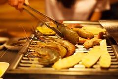 Mat för hållande rostfritt stål för kvinnahand som varm griper tångklämman som steker kött- och grönsakmat på grillfestgallerpann arkivbild