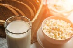 Mat för mejerilantgård: ostmassaost och kräm i bunkar, mjölkar och nytt bröd, solljuseffekt, selektiv fokus Arkivfoto