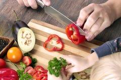 Mat, familjen, matlagning och folkbegreppet - Man att hugga av paprika på skärbräda med kniven i kök med dottern Arkivfoton