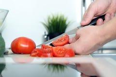 Mat, familjen, matlagning och folkbegreppet - Man att hugga av tomaten på skärbräda med kniven i kök royaltyfri foto