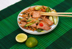 Mat with fried short rice noodles and meat. Fried short rice noodles with meat on mat Royalty Free Stock Image