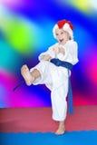 On the mat, girl beats a kick leg Royalty Free Stock Photo