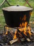 Mat i en kittel på en brand Matlagning utomhus i järn- kittel Arkivbilder