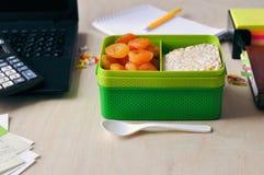 Mat i kontoret eller på skola Äta lunch asken med sund mat på skrivbordet arkivbilder