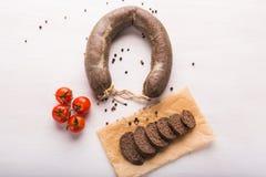 Mat, kokkonst och hamburgerköttbegreppet - stäng sig upp av köttkorven med tomater och peppar på kraft papper royaltyfri fotografi