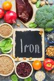 Mat med järn, lever, granatäpple, muttrar, persimon, äpplen, bönor, linser, broccoli, bovete, spenat, sesam på en lantlig baksida royaltyfri fotografi