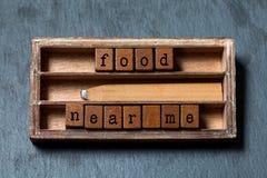 Mat nära mig begreppsmässig text Träaskar med bokstäver, retro blyertspenna, åldras askbakgrund Grå sten, makro som är mjuk Fotografering för Bildbyråer