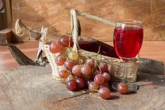 Mat- och drinkbakgrund med rött vin, nya druvor och wineflaskan Royaltyfri Bild