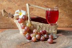 Mat- och drinkbakgrund med rött vin, nya druvor och wineflaskan Arkivfoto