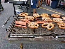 Mat på ett stort BBQ-galler, en grillfest, varmkorvar och mjuka kringlor arkivfoto