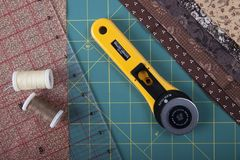 Knife for patchwork on mate for patchwork. On the mat for patchwork sewing  a knife for patchwork, a ruler, a patchwork napkin and threads Stock Images
