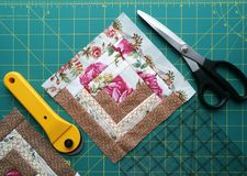 Tools for patchwork on the mat for patchwork. On the mat for patchwork sewing there are scissors, a knife for patchwork, a ruler, a patchwork napkin Royalty Free Stock Images