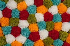 Mat of pompons made from multi-colored handmade yarn royalty free stock photography