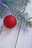 Mat red christmas ball and pinetree branch on white wooden board Royalty Free Stock Image