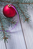 Mat red christmas ball and pinetree branch on white wooden board Stock Image