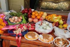 Mat sattes som offerings på en tabell i borggården av en buddistisk tempel i Suphan Buri (Thailand) royaltyfria bilder