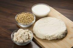 Mat: Sojabönor mjölkar, sojabönor, Okara och tofuen på träbakgrund arkivfoto