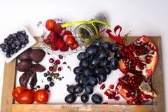 mat som är rik med resveratrolen, druvor, plommoner, jordgubbe, mörk choklad, granatäpple, tranbär, grönt te, tomater, blåbär royaltyfri bild