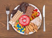 Mat som innehåller för mycket socker på en platta royaltyfria bilder