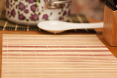 Mat for sushi with the preparation dishes in background Royalty Free Stock Photo