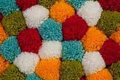 Mat van pompons van multi-colored met de hand gemaakt garen worden gemaakt dat stock foto