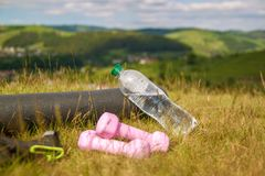 Mat, water and dumbbells on the grass on the mountain in the background of a beautiful landscape. stock photography