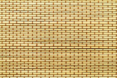 Mat from yellow wood bamboo sticks with brown thread Stock Photo