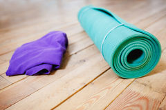 Mat for yoga rolled-up on wooden floor Stock Photos