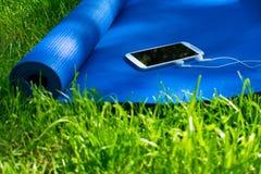 Mata dla, telefon z he?mofonami na zielonej trawie i, fotografia stock