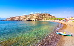 Matala beach with caves on the rocks, Crete, Greece. Matala beach with caves on the rocks that were used as a roman cemetery and at the decade of 70`s were stock photo